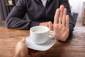 person putting hand up to refuse cup of coffee