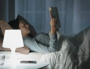 woman reading book in bed with lamp on