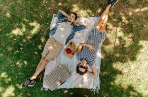 couple relaxing on blanket in the shade with snacks