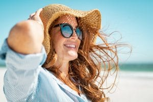 woman wearing hat and sunglasses at the beach