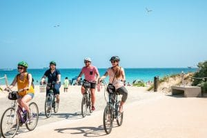 Group riding bikes on the beach