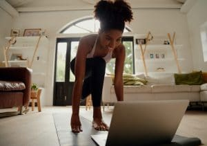 woman exercising in her living room using her laptop