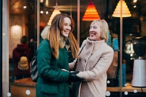 adult daughter and older mother embracing and smiling outside of a store