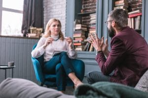 female therapist talking to male patient in comfortable office