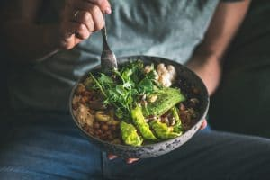 woman in t-shirt and jeans eating a buddha bowl