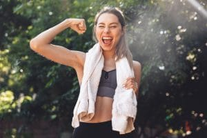 young woman flexing after her outdoor workout