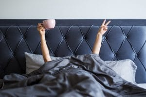 woman just waking up in bed with arms up, one hand with coffee mug and the other a peace sign