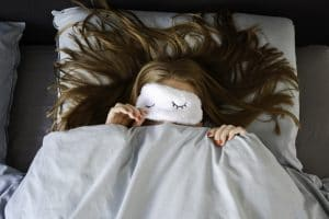 young woman sleeping in her bed with an eye mask and covers over her mouth.