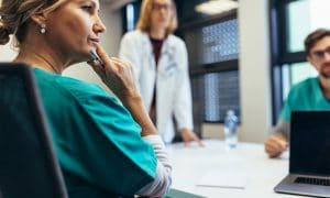 nurse sitting at conference room table with other medical professionals thinking about issue.