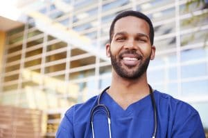 black male nurse standing outside hospital in blue scrubs with a smile on his face