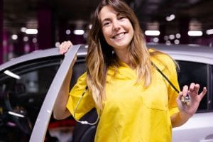 young travel nurse smiling and getting out of her car