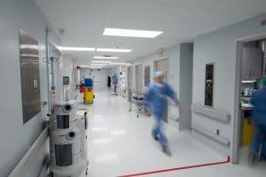 nurse walking swiftly down hospital hallway